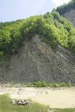 Bloße Klippe mit einem Wald auf die Oberseite Stockfotos
