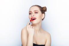 Bloße Schultertat der jungen hübschen Brötchenfrisur des Makes-up der Frau modischen hellen roten Lippender Affe mit weißem Studi Stockfoto
