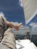 Bloßer Fuß eines Mannes, der auf der Plattform der Yacht liegt Stockfoto