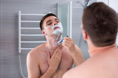 Bloßer Mann, der seinen Kasten rasiert und den Spiegel betrachtet Stockbild