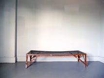 Bloßes Metallfeldbett im grunge Raum Stockfotografie