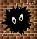 Blob on a brick wall. On the wall of red brick a big black blob with eyes Stock Image