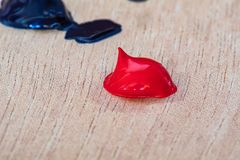 A Blob/Dab of Red Acrylic Paint on a wood Artist`s palette ready to be used by a working artist. A Blob/Dab of Red Acrylic Paint on a wood Artist`s palette. in stock photography