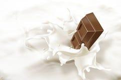 Bloc de chocolat tombant dans une mer de lait. Images libres de droits
