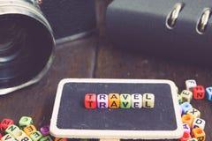 Bloc de mot de VOYAGE sur l'appareil-photo en bois de signage et de vintage couleur fanée d'effet Photographie stock