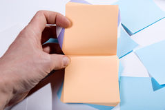 Bloc de notes de post-it. Main tenant les pages vides pour des notes Photographie stock