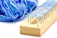 Bloc de tricotage en bois et amorçage bleu Photographie stock libre de droits