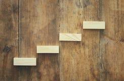 bloc en bois aranging empilant comme escaliers d'étape au-dessus de table en bois concept d'affaires et de croissance Photographie stock