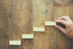 bloc en bois aranging empilant comme escaliers d'étape au-dessus de table en bois concept d'affaires et de croissance Photo libre de droits