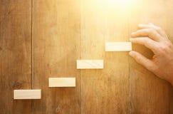 bloc en bois aranging empilant comme escaliers d'étape au-dessus de table en bois concept d'affaires et de croissance Photographie stock libre de droits