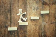 bloc en bois aranging empilant comme escaliers d'étape au-dessus de table en bois concept d'affaires et de croissance image libre de droits
