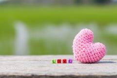 Bloc en bois des textes avec le coeur rose pour l'amour Photographie stock libre de droits