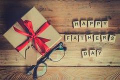 Bloc et boîte-cadeau heureux de jour du ` s de père avec des verres sur le backg en bois Image stock