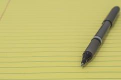 Bloc jaune avec le stylo 4 Photographie stock