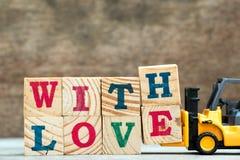 Bloc jaune H et E de lettre de prise de chariot élévateur de jouet au mot avec amour Image libre de droits
