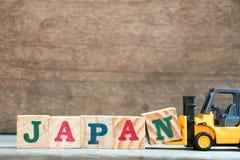 Bloc jaune N de lettre de prise de chariot élévateur de jouet pour accomplir le mot Japon photo stock