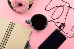 Bloc-notes aux ressorts, à une tasse de café et à un téléphone avec des écouteurs sur un fond rose lumineux Place pour le texte l Images stock