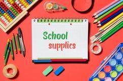 Bloc-notes avec des mots de fournitures scolaires, fond rouge Photographie stock