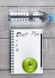 Bloc - notes avec des pommes et eau comme idée de régime Photo libre de droits