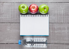 Bloc - notes avec des pommes et eau comme idée de régime Images libres de droits