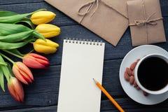 Bloc-notes avec le crayon à côté des tulipes, du café, et des enveloppes sur le fond en bois Vue de ci-dessus avec l'espace de co Photographie stock libre de droits
