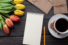 Bloc-notes avec le crayon à côté des tulipes, du café, et des enveloppes sur le fond en bois Vue de ci-dessus avec l'espace de co Photo libre de droits