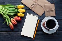 Bloc-notes avec le crayon à côté des tulipes, du café, et des enveloppes sur le fond en bois Vue de ci-dessus avec l'espace de co Photographie stock