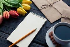 Bloc-notes avec le crayon à côté des tulipes, du café, et des enveloppes sur le fond en bois Vue de ci-dessus avec l'espace de co Images stock