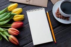 Bloc-notes avec le crayon à côté des tulipes, du café, et des enveloppes sur le fond en bois Vue de ci-dessus avec l'espace de co Photos stock