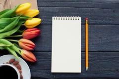 Bloc-notes avec le crayon à côté des tulipes, du café, et des enveloppes sur le fond en bois Vue de ci-dessus avec l'espace de co Image stock