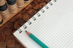 Bloc-notes avec le crayon et l'abaque sur pièces de monnaie Image stock