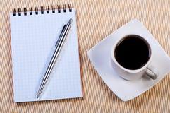Bloc-notes avec le crayon lecteur et le café. Photo libre de droits