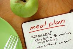 Bloc-notes avec le plan et la pomme de repas de mots image stock