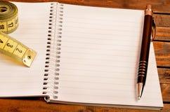 Bloc-notes avec le stylo et le centimètre Photos stock