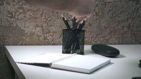Bloc-notes avec un crayon sur une table blanche banque de vidéos
