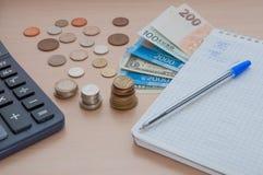 Bloc-notes avec un stylo, des factures, un divers argent et une calculatrice sur la table Image libre de droits