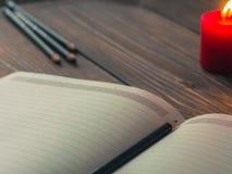 Bloc-notes blanc vide avec des crayons sur la table en bois, bougie sur le fond Photographie stock