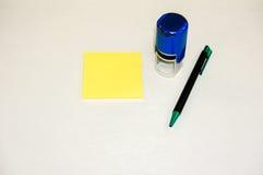 Bloc-notes collant jaune, tampon en caoutchouc rond et stylo Image stock