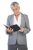 Bloc-notes concentré de lecture de femme d'affaires photo stock