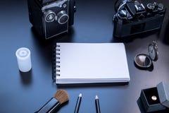 Bloc-notes, crayons, montre, appareil-photo, brosse et giftbox sur le blac de PVCboard Images stock