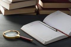 Bloc-notes dans la boîte avec un stylo sur une table en bois à l'arrière-plan d'une pile de livres Image libre de droits