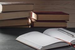 Bloc-notes dans la boîte avec un stylo sur une table en bois à l'arrière-plan d'une pile de livres Photographie stock libre de droits