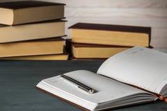 Bloc-notes dans la boîte avec un stylo sur une table en bois à l'arrière-plan d'une pile de livres Photos stock