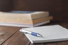 Bloc-notes dans la boîte avec un stylo sur une table en bois Images libres de droits
