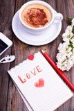 Bloc-notes dans une ligne avec un crayon rouge d'amour d'inscription Photographie stock libre de droits