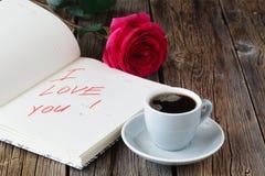 Bloc-notes de lettre d'amour, roses rouges et tasse de café sur la table en bois Concept de jour de Valentines Photo libre de droits