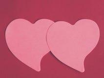 Bloc-notes deux en forme de coeur rose sur le fond en cuir rouge Images stock
