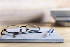 Bloc-notes en boîte avec un stylo et verres sur un en bois Photographie stock libre de droits