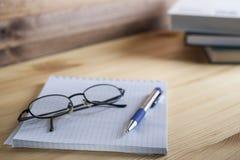 Bloc-notes en boîte avec un stylo et verres sur une table en bois à l'arrière-plan d'une pile de livres Photographie stock