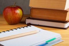 Bloc-notes en boîte avec un stylo et verres sur une table en bois Photo libre de droits
